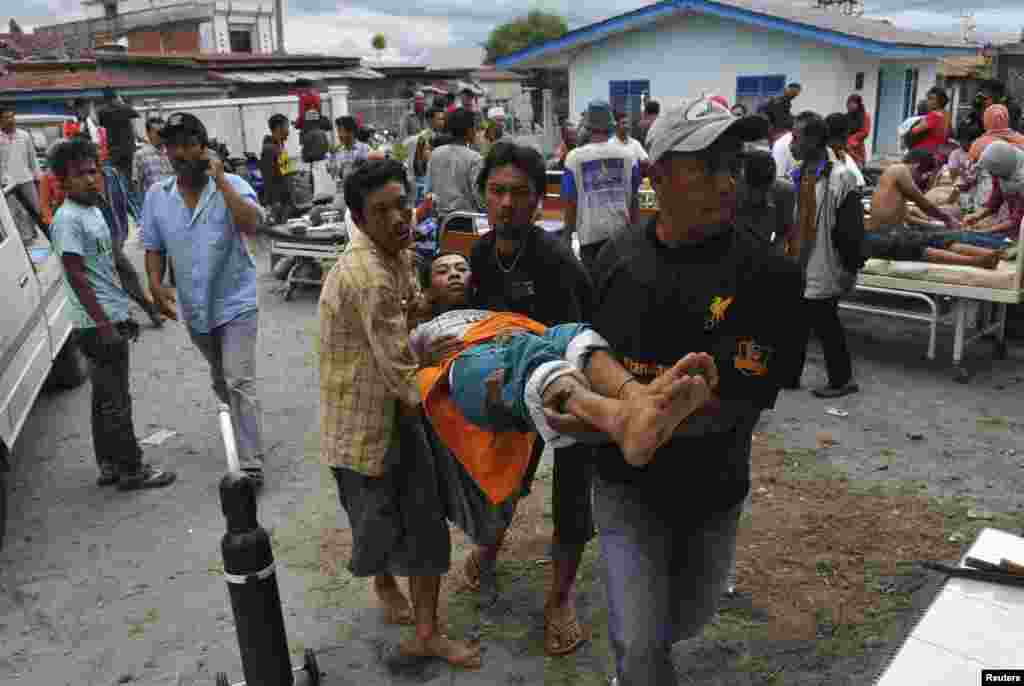 An injured resident is evacuated to the local clinic after a strong earthquake hit in Bener Meriah district in Central Aceh, July 2, 2013.
