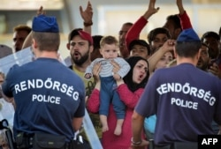 Hungarian police officers face a group of Syrian migrants, with a woman holding a baby, on the platform of the Kobanya-Kispest station, Budapest suburb, on Sept. 2, 2015, as the refugees refused to board a train to the Debrecen camp.