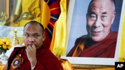FILE - Tibetan spiritual leader Ogyen Trinley Dorje, the 17th Karmapa, looks on as he sits in front of a portrait of the Dalai Lama during a function commemorating the 50th anniversary of the Tibetan Institute of Medicine and Astrology in Dharmsala, India, June 2, 2011.