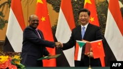 Chinese President Xi Jinping (R) shakes hands with Sudanese President Omar al-Bashir during a signing ceremony at the Great Hall of the People in Beijing, Sept. 1, 2015.