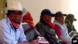 Các thành viên mang mặt nạ của đơn vị bảo vệ cộng đồng, trong thị trấn Los Reyes ở Michoacan, Mexico, 29/7/2013