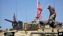 This April. 29, 2017, still taken from video, shows an American soldier standing on an armored vehicle in the northern village of Darbasiyah, Syria.