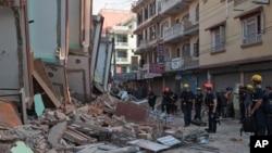 Para petugas keselamatan berdiri di samping gedung yang ambruk akibat gempa di Kathmandu (12/5). (AP/Ranup Shrestha)