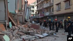 Rescue workers stand beside buildings that collapsed in an earthquake in Kathmandu, Nepal, Tuesday, May 12, 2015. A major earthquake has hit Nepal near the Chinese border between the capital of Kathmandu and Mount Everest less than three weeks after the country was devastated by a quake. (AP Photo/Ranup Shrestha)