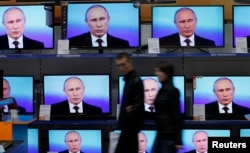 FILE - Visitors walk past TV sets during Russian President Vladimir Putin's live broadcast nationwide phone-in at the DNS electronic shop in Russia's Siberian city of Krasnoyarsk April 17, 2014.