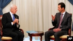 FILE - This SANA photo shows Syrian President Bashar Assad, right, speaking with U.N. envoy Staffan de Mistura in Damascus, Nov. 10, 2014.