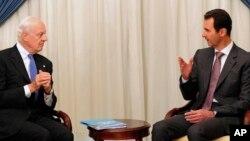 FILE - This SANA photo shows Syrian President Bashar al-Assad, right, speaking with U.N. envoy Staffan de Mistura in Damascus, Nov. 10, 2014.
