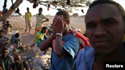 FILE - An illegal immigrant from Ethiopia covers his face as he waits with others for a boat to cross into Yemen outside the town of Obock, north Djibouti.