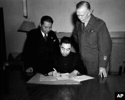 ນາຍພົນ Chou En-Lai, ຕາງໜ້າ ພັກຄອມມິວນິສ ລົງນາມຄຳສັງຢຸດຍິງ ຢູ່ທີ່ Chungking, ປະເທດຈີນ, ວັນທີ 10 ມັງກອນ 1946 ຊຶ່ງນຳມາການຍຸຕິ ຂໍ້ຂັດແຍ່ງຂອງພົນລະເມືອງ ໃນຈີນ. ນາຍພົນ George Marshall, ທູດພິເສດ ສະຫະລັດ ປະຈຳ ຈີນ, ຂວາ, ແລະ ຜູ້ປົກຄອງ ທ່ານ Chang Chun.