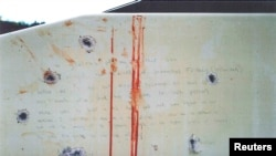 A blood-stained message that prosecutors say Boston Marathon bombing suspect Dzhokhar Tsarnaev wrote on the inside of a boat is seen with bullet holes in an undated evidence picture shown to jurors in Boston, March 10, 2015.