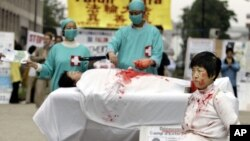 一名法輪功學員在歐洲委員會前抗議他們所說的中國摘除法輪功學員器官的犯罪行為。 (2006年6月15日)