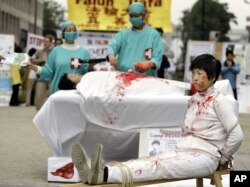 FILE – Falun Gong practitioners simulate organ harvesting in a mock Chinese labor camp in front of the Presidential Office in Taipei, Taiwan, April 23, 2006, in protest against China's suspected abuse and killing of Falun Gong members.