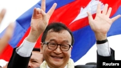 Sam Rainsy, president of the National Rescue Party, greets his supporters in Phnom Penh, July 19, 2013.