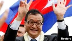 Pemimpin oposisi Kamboja, Sam Rainsy, melambai kepada para pendukungnya di Phnom Penh (19/7). Permohonan Sam Rainsy untuk mencalonkan diri dalam pemilu parlemen ditolak.