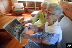 Joan Rodby (left) and Emma Veary look at their fifth-grade class photo during a reunion in Makawao, Hawaii.