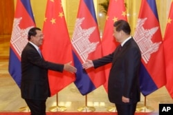 FILE - Cambodian Prime Minister Hun Sen, left, shakes hands with China's President Xi Jinping before a meeting at the Great Hall of the People in Beijing Friday, Nov. 7, 2014.