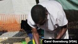 Un travailleur de la santé chargé de lutter contre le virus à Ebola en Guinée (Carol Guensburg, VOA)