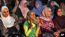 "A girl in the women's section of the audience claps as she watches the filming of a new Islamic version of ""American Idol,"" launched to promote and drum up talent for the Arab world's first Islamic pop music video in a bid to capitalize on a generation of"