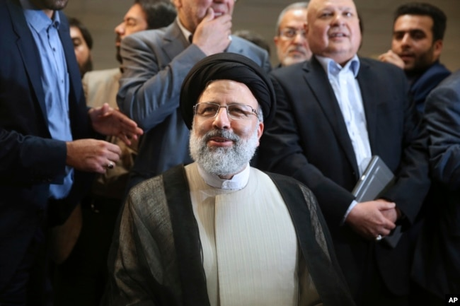 FILE - Iranian cleric Ebrahim Raisi registers his candidacy for the May 19 presidential elections at the Interior Ministry in Tehran, Iran, April 14, 2017. Over 1,600 people registered to run. Under Iranian law, there's no fee for registering.