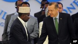 Somalia's PM Abdiweli Mohamed Ali, left, shakes hands with Turkish counterpart before he addresses a conference that aims to support Somalia in a transition process, Istanbul, Turkey, June 1, 2012.