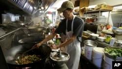 康涅狄克州一家餐厅的厨房里,一名厨师正进行烹饪。