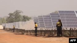 FILE - People stand next to solar panels of the solar energy power plant in Zagtouli, near Ouagadougou, Burkina Faso, Nov. 29, 2017, on its inauguration day.