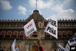 "People hold signs reading ""Pena out,"" and ""No more gasoline price hikes"" as they protest in front of the National Palace in Mexico City, Jan. 1, 2017."