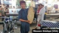 ایک نوعمر لڑکا قندھاری نان دکھاتے ہوئے