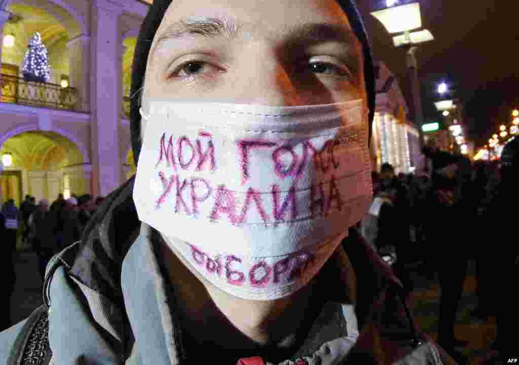 """Một người biểu tình tại một cuộc tụ tập tại trung tâm St. Petersburg. Biểu ngữ có dòng chữ: """"Phiếu của tôi bị lấy cắp trong cuộc bầu cử."""" (AP/Dmitry Lovetsky)"""