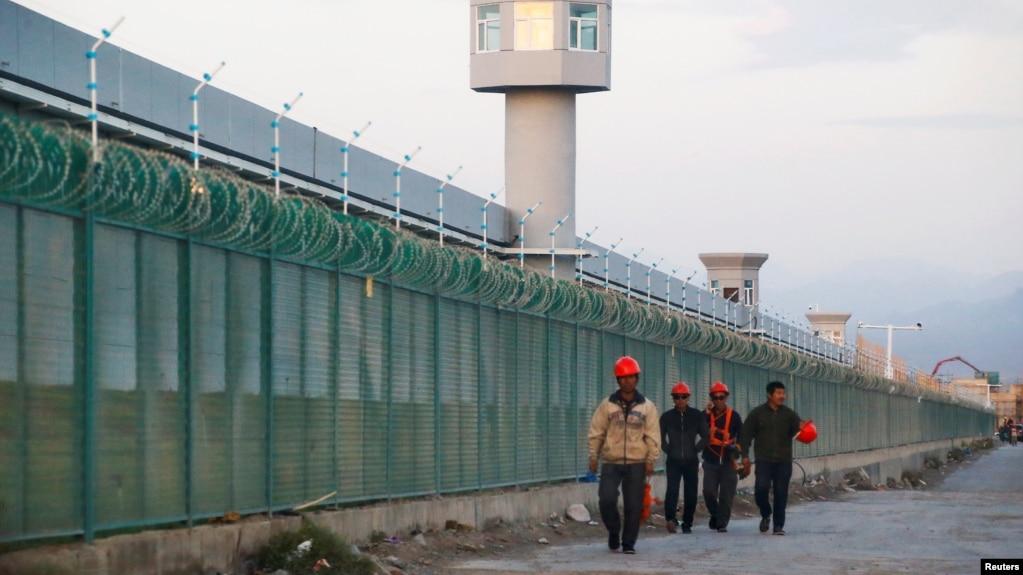 Công nhân đi ngang tường rào của một nơi được chính thức gọi là trung tâm dạy nghề ở Urumqi, thủ phủ của Khu Tự trị Uighur Tân Cương, ngày 4 tháng 9, 2018.