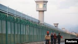 中國新疆維吾爾自治區達坂城的官方所謂的職業技能教育中心的圍欄旁邊,有工人走過。(2018年9月4日)