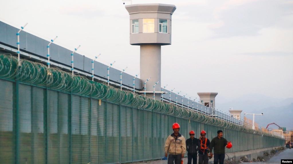 Tư liệu: Công nhân đi ngang qua một trại cải tạo có hàng rào vây quanh, mà chính quyền gọi là 'trung tâm huấn nghiệp' tại Dabancheng ở vùng Tân Cương, TQ, ngày 4/9/2018. REUTERS/Thomas Peter