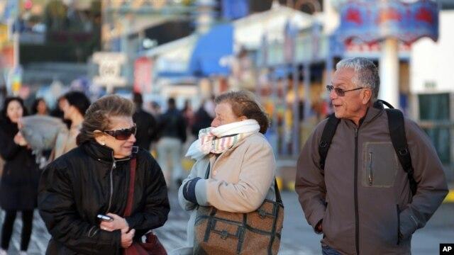 Visitantes en California soportan los fuertes vientos y las gélidas temperaturas de esta temporada.