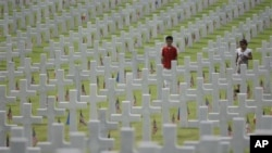 Children walk along layers of tombs as they attend Memorial Day ceremonies at the Manila American Cemtery and Memorial in suburban Taguig, south of Manila, Philippines on Sunday May 29, 2011. The cemetery site contains the largest number of U.S. military