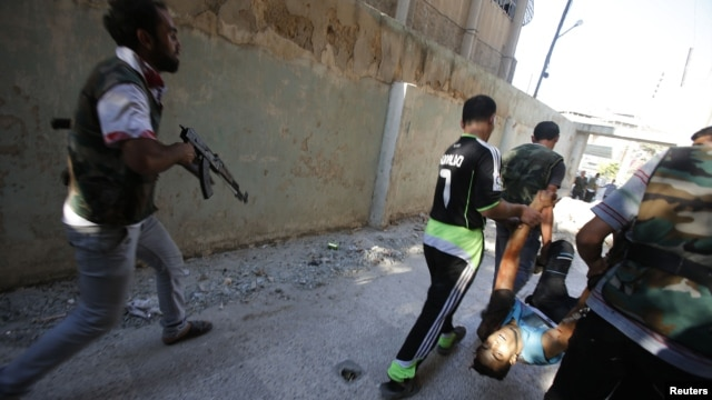 Free Syrian Army fighters carry the body of a fellow fighter after he was shot by a sniper at Seif a Dawla district in Syria's northwestern city of Aleppo September 4, 2012.