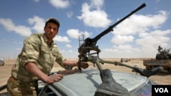 Seorang tentara pemberontak Libya siaga dengan senjata mesin.