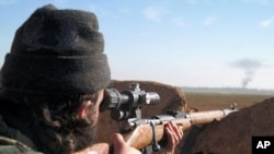A militant fighter aims a sniper rifle during fighting in Tal Tamr, Hassakeh province, Syria, in this image posted by the Al-Baraka division of the Islamic State group, Feb. 24, 2015.