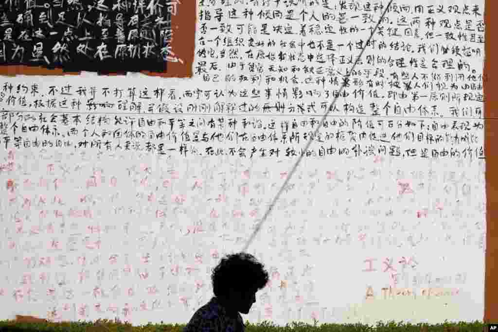 "A woman walks past a wall covered with Chinese characters from chapters of John Rawls' book ""A Theory of Justice"" outside an art gallery in Beijing."