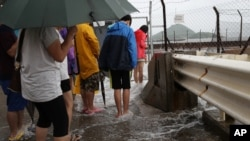 People play with overflown water caused by Typhoon Nida in Hong Kong, Tuesday, Aug. 2, 2016.