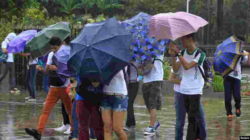 """Participants for """"Walk for Peace"""" use umbrellas in the rain brought on by Typhoon Kalmaegi, also called Luis, at Luneta park in Manila, Philippines, Sept. 14, 2014."""