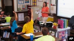 FILE - In this Sept. 18, 2013 file photo, Shelly Ellis teaches fourth-grade students in a newly air conditioned classroom at Bement Elementary School in Bement, Ill. AP Photo/David Mercer, File)