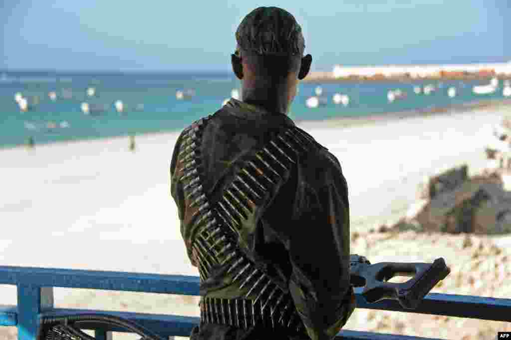 A Somali soldier looks at Lido Beach from the terrace of the Lido restaurant, following Thursday's overnight attack in Mogadishu. Islamist al-Shabab militants killed at least 19 people when five gunmen detonated a bomb before storming the popular seaside restaurant.
