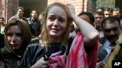 Czech model Tereza Hluskova, center, reacts after appearing in court in Lahore, Pakistan, March 20, 2019.