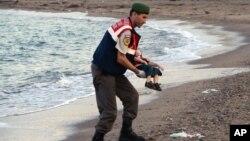 Polisi paramiliter menggendong mayat anak migran yang tidak diidentifikasi, di pantai dekat Bodrum, Turki (2/9).