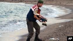 A paramilitary police officer carries the lifeless body of a migrant child, later identified as that of three-year-old Aylan Al Kurdi, near the Turkish resort of Bodrum, Sept. 2, 2015.