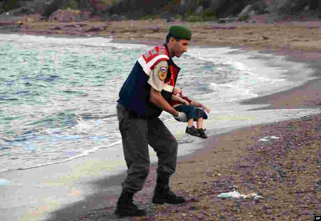 A paramilitary police officer carries the lifeless body of a migrant child, lifting it from the seashore near the Turkish resort of Bodrum, Sept. 2, 2015.