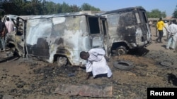 A boy searches the ground next to a burnt-out vehicle, caused by an attack from Boko Haram militants, in Bama, Borno State, Nigeria, Feb. 20, 2014.