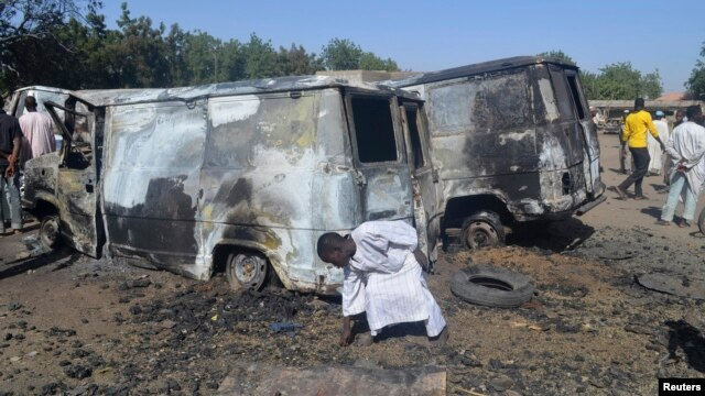 A boy searches the ground next to a burnt-out vehicle, caused by an attack by Boko Haram militants in Bama, Borno State, February 20, 2014.