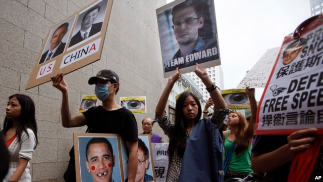 Supporters of Edward Snowden, a former CIA employee who leaked top-secret information about U.S. surveillance programs, hold placards as they march to the Consulate General of the United States in Hong Kong, June 15, 2013.