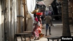 FILE - Women walk through a market deserted following protests in Bujumbura, April 29, 2015.